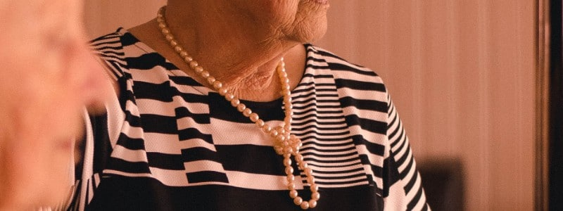 old person with pearl necklace
